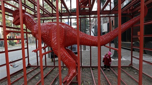 A child looks at a dinosaur sculpture designed by Chinese artist Sui Jianguo at the 798 Art District in Beijing on Wednesday, Nov. 21, 2012. The 798 Art District, often compared to New York City's Greenwich Village, is a thriving community of about 400 galleries, shops and restaurants on the eastern edge of Beijing housed in a complex of former electronics factories built with the help of East Germany in the 1950s.