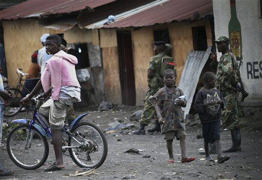 Children walk past M23 rebels in the eastern Congo town of Sake, some 27 kms west of Goma on Thursday Nov. 29, 2012. Rebels, who last week seized one of the most important cities in eastern Congo and advanced beyond, said Thursday they had pulled back several miles to the town of Sake and were on track to leave the key city of Goma by Friday, in accordance with a deadline imposed by the international community.