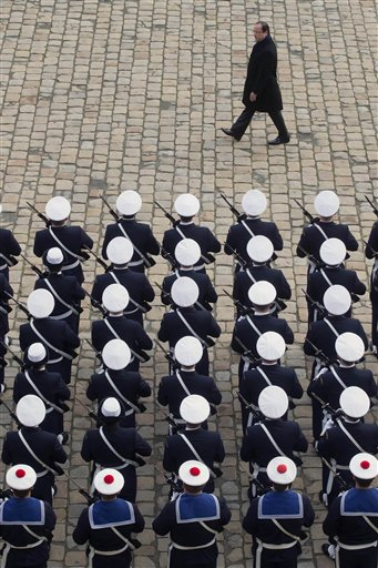 French President Francois Hollande (back) reviews the troops during a biannual military ceremony at the Les Invalides in Paris on Thursday, Nov. 29, 2012.