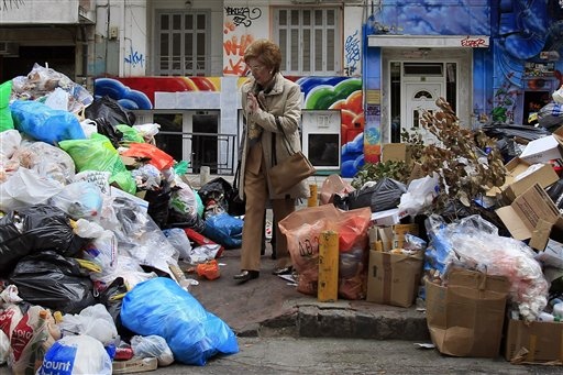 Two women pass among piles of garbage amassed during successive strikes by municipal workers in the northern Greek port city of Thessaloniki on Sunday, Nov. 25, 2012. Government plans to place 2,000 civil servants on notice ahead of reassignment or potential dismissal.