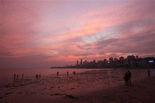 Indians stand on the Arabian Sea coast after sunset in Mumbai, India on Thursday, Nov. 1, 2012.