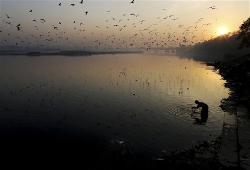 A Hindu devotee offers prayers in the River Yamuna during Karthik Purnima in New Delhi, India on Wednesday, Nov. 28, 2012. Karthik Purnima is celebrated on the full moon day of the Hindu calendar month of Karthik and considered very auspicious by Hindus.