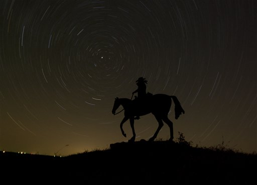 In this photo made using an hourlong time exposure, stars swirl behind a sign for a ranch near Olsburg, Kan. early Tuesday morning, Nov. 13, 2012.