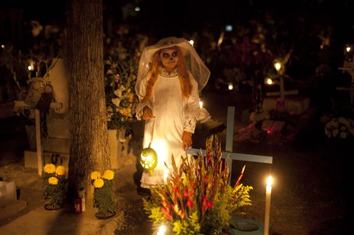 Frangerato Salvador, 8, dressed as a Katarina, stands beside her brother's grave, marking the Day of the Dead holiday at the cemetery in San Gregorio, Mexico, Thursday, Nov. 1, 2012. The holiday honors the dead on Nov. 1, coinciding with All Saints Day and All Souls' Day on Nov. 2.