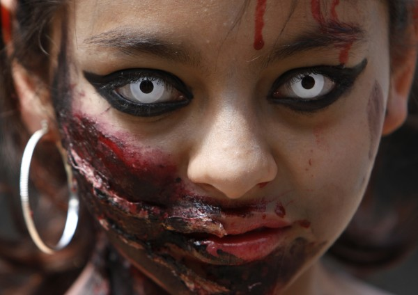 A woman in zombie make-up looks at the camera as she takes part in the Zombie Walk in Mexico City, Saturday, Nov. 3, 2012. According to the organization Zombie Walk Mexico, they are trying to set a new Guinness World Record for the biggest Zombie Walk.