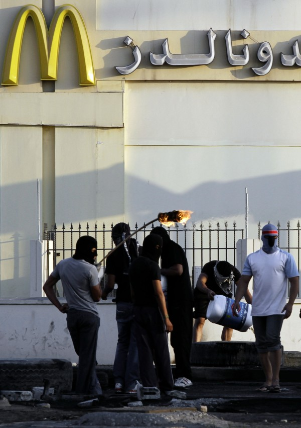 Masked Bahraini anti-government protesters pour petrol on tires to set them on fire near a shopping center at the edge of the western village of Malkiya, Bahrain, Monday, Nov. 12, 2012. Tire fires are a common site in restive villages across the Gulf island kingdom. Arabic writing reads, &quotMcDonald's.&quot