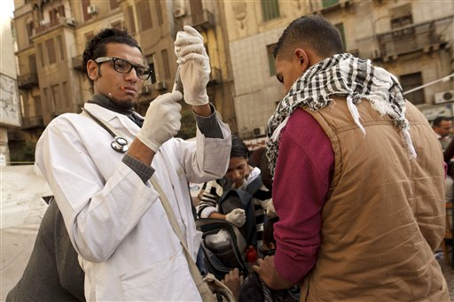 A volunteer doctor prepares an injection for a protester, wounded during clashes with security forces, at a field hospital in Tahrir Square in Cairo, Egypt on Thursday, Nov. 29, 2012. Members of an Islamist-dominated panel tasked with writing Egypt's new constitution are gathering to vote on the document's final draft in Cairo, where dozens of opposition supporters are still camped out at Tahrir Square.