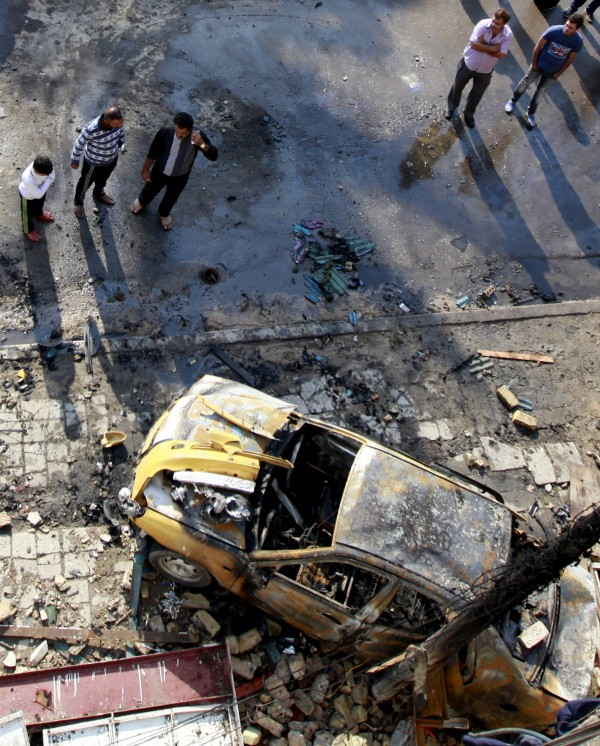 People gather at the scene of a car bomb attack in central Baghdad, Iraq, Wednesday, Nov. 14, 2012. Iraqi insurgents unleashed a new wave of bombings across the country early Wednesday targeting security forces and civilians, killing and wounding scores of people, police said.