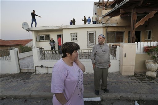 Residents inspect the damage at a house after a rocket fired by Palestinian militants from inside the Gaza Strip, landed at the community of Ofakim, in southern Israel, Sunday, Nov. 18, 2012. According to reports , two Israelis were wounded and their condition is unknown. Israel launched the operation last Wednesday by assassinating Hamas' military chief and carrying out dozens of airstrikes on rocket launchers and weapons storage sites. Over the weekend, the operation began to target Hamas government installations as well, including the offices of its prime minister and attacks on a major training base and the two media centers.