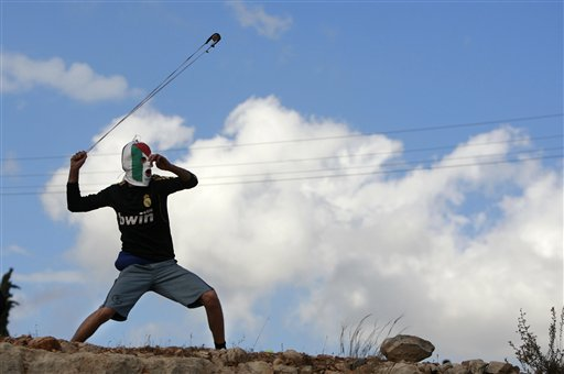 A Palestinian protester hurls a stone at Israeli security forces during a protest against the expansion of the nearby Jewish settlement of Halamish, in the West Bank village of Nabi Saleh near Ramallah, Friday, Nov. 9, 2012.