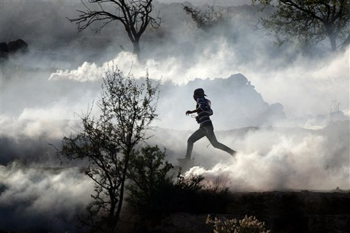 A Palestinian demonstrator runs through a cloud of tear gas during clashes against Israel's operations in Gaza Strip, outside Ofer, an Israeli military prison near the West Bank city of Ramallah, Thursday, Nov. 15, 2012. Meanwhile, Palestinian President Mahmoud Abbas cut short a trip to Europe to deal with the crisis.