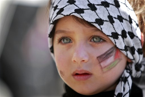 A girl with the Palestinian flag painted  on her face attends a rally supporting the Palestinian UN bid for observer state status, in the West bank city of Ramallah, Thursday, Nov. 29, 2012. The Palestinians are certain to win U.N. recognition as a state on Thursday but success could exact a high price: delaying an independent state of Palestine because of Israel's vehement opposition.