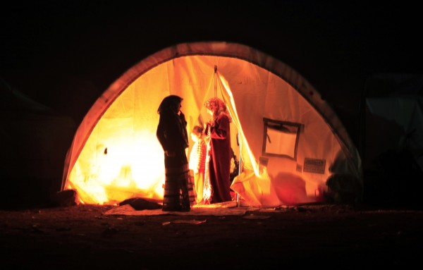 A Syrian family who fled the violence in their village set up a fire inside their tent at a camp in the Syrian village of Atma, near the Turkish border with Syria, Sunday, Nov. 4, 2012.