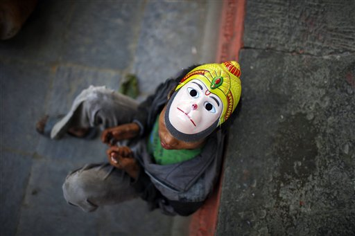 A Nepalese street child, wearing a mask of Hindu monkey God Hanuman, rests on a street in Katmandu, Nepal on Friday, Nov. 2, 2012.