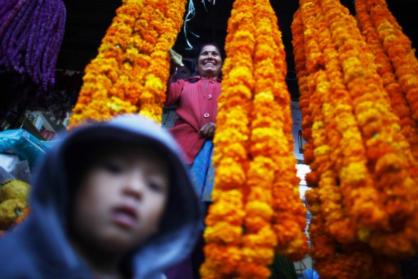 A flower vendor woman smiles as she waits for the customer during Tihar festival in Katmandu, Nepal, Monday, Nov 12, 2012. Tihar, the festival of lights is one of the most important of all Hindu festival, where they worship Goddess Laxmi, the Goddess of wealth and decorated their houses with oil lamps. The five-day festival starting from the thirteenth day of the waning moon in October also meant for life and prosperity.