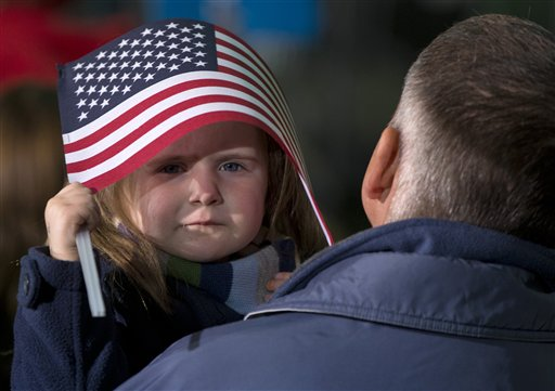 A little girl takes shelter under an American Flag before President Barack Obama arrives to speak at a campaign event at the Franklin County Fairgrounds, Friday, Nov. 2, 2012, in Hilliard, Ohio, before heading to another campaign stop in in Springfield, Ohio.
