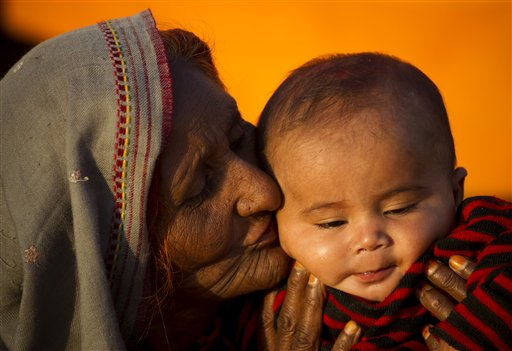 Pakistani nomad woman Zakia kisses her grandson in Islamabad, Pakistan on Friday, Nov. 9, 2012.