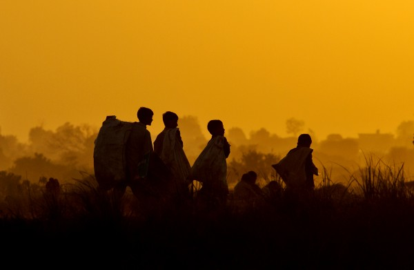 Pakistani boys, who collect recycled items for their living, are silhouetted against sunset while they heading home after a day of work on the outskirts of Islamabad, Pakistan on Sunday, Nov. 4, 2012.