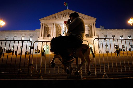 A protester blows a horn while seated on a toy horse outside the Portuguese parliament in Lisbon on Thursday, Nov. 29, 2012, during a protest by fun-fair workers against the planned increase of VAT tax that they claim will ruin their business.