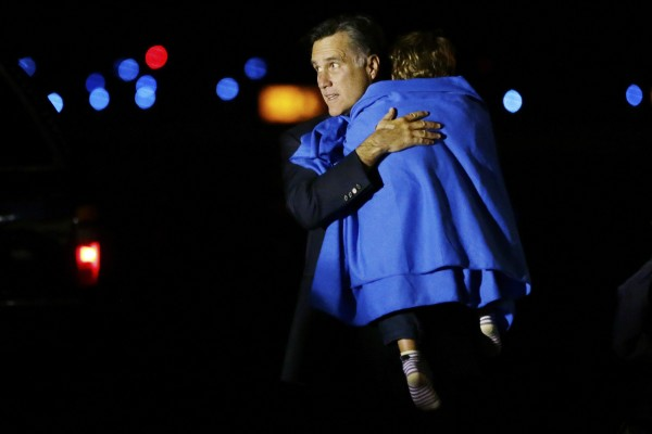 Republican presidential candidate and former Massachusetts Gov. Mitt Romney carries one of his grandsons as he steps off his campaign plane at Pease International Airport in Portsmouth, N.H., early Saturday, Nov. 3, 2012, as they arrive from Cincinnati, Ohio.