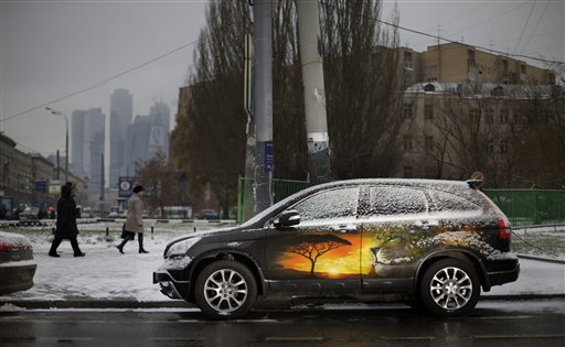 A brightly painted car is parked along a snowy street in Moscow, Russia on Monday, Nov. 26, 2012. Light snowfall hit Moscow this morning, testing the city's winter readiness.