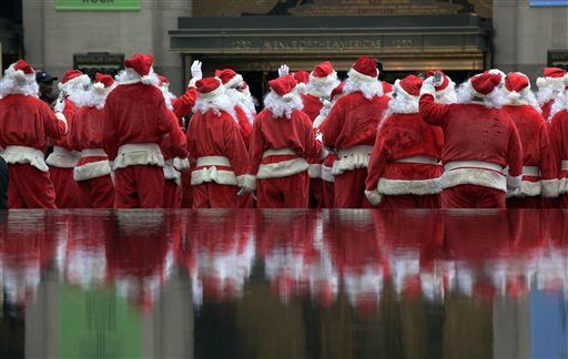 Volunteers of America Santas are reflected in a fountain during their 110th annual Sidewalk Santa Parade, in New York on Friday, Nov. 23, 2012. The donations they raise are used for a holiday food voucher program for needy residents.
