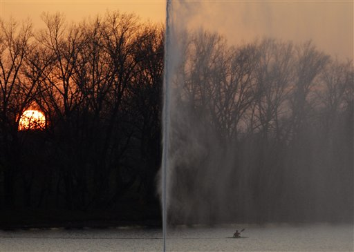 A man paddles his kayak by the fountain that looks like a geyser during sunset at the Ada Ciganlija Lake in Belgrade, Serbia on Monday, Nov. 26, 2012. Weather forecast predicts good autumnal weather conditions in Serbia for the coming days.