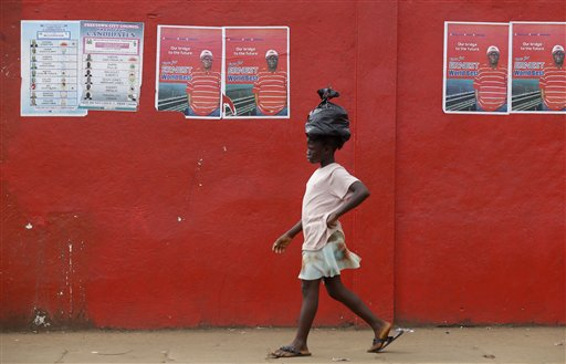 A girl walks past election posters for incumbent President Ernest Bai Koroma, in Freetown, Sierra Leone, Sunday, Nov. 18, 2012. Sierra Leoneans chose Saturday between keeping an incumbent president who has expanded health care and paved roads or electing an opposition candidate to lead this war-scarred nation still recovering a decade later despite its mineral riches. Election results were still being compiled on Sunday.