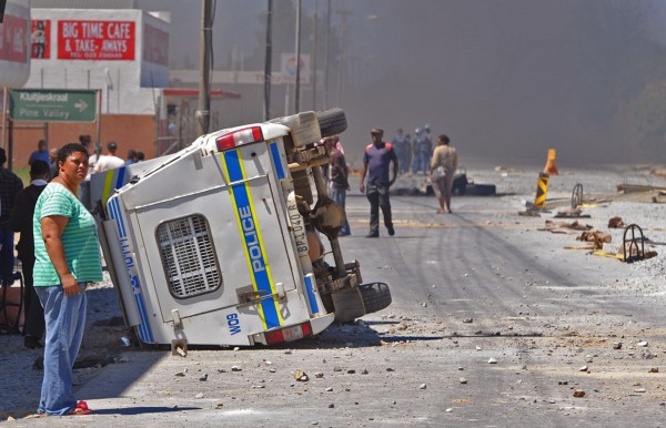 A South African Police truck (left) that was overturned by farm workers after they went on a rampage in Wolseley, South Africa, Wednesday, Nov. 14, 2012. Violent protests by farm workers have erupted in South Africa after weeks of unrest in the country's mining industry. Television images showed protesters overturn a police truck and set fires in the streets Wednesday in a town in South Africa's Western Cape. The workers have been protesting their wages, saying they want a minimum wage of $17 a day. Currently, workers make about half that amount a day.
