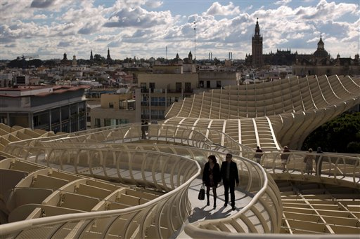 A couple walk along of one the corridors of the Metropol Parasol, overseeing the old city and the Giralda Cathedral of Seville, Spain, Sunday, Nov. 18, 2012. The Metropol Parasol by Jurgen Mayer H. Architects claims to be the world's largest wooden structure.