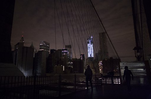 Much of lower Manhattan remains dark, as viewed from the darkened Manhattan side of the pedestrian walkway of the Brooklyn Bridge, Thursday, Nov. 1, 2012 in New York. In the wake of superstorm Sandy, power outages still plague much of the New York area.