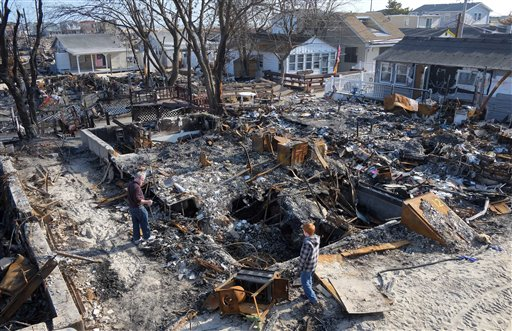 John Hardy (left) and his son, Liam, 13, visit the charred remains of his wife's parents home in the Breezy Point section of the Queens borough of New York on Friday, Nov. 23, 2012. A fire destroyed more than 100 homes in the oceanfront community during Superstorm Sandy.