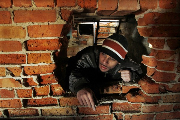 Chris Santos looks through a hole in a partially collapsed basement wall of an oceanfront home, Sunday, Nov. 4, 2012, in Belmar, N.J., as he checks for severe structural problems in foundation and basement damage from Monday's storm surge by Superstorm Sandy.