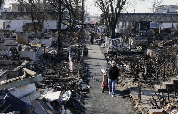 Louise McCarthy carts belongings from her flood-damaged home as she passes the charred ruins of other homes in the Breezy Point section of the Queens borough of New York, Wednesday, Nov. 14, 2012. A fire destroyed more than 100 homes in the oceanfront community during Superstorm Sandy.