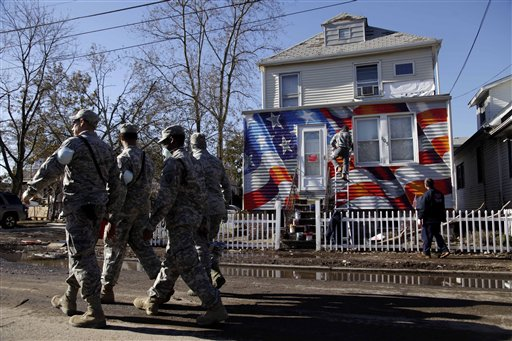 Members of the National Guard walk past a house damaged by superstorm Sandy as it is painted with an American flag in the New Dorp section of Staten Island, New York, Tuesday, Nov. 6, 2012. Voting in the U.S. presidential election is the latest challenge for the hundreds of thousands of people in the New York-New Jersey area still affected by superstorm Sandy.