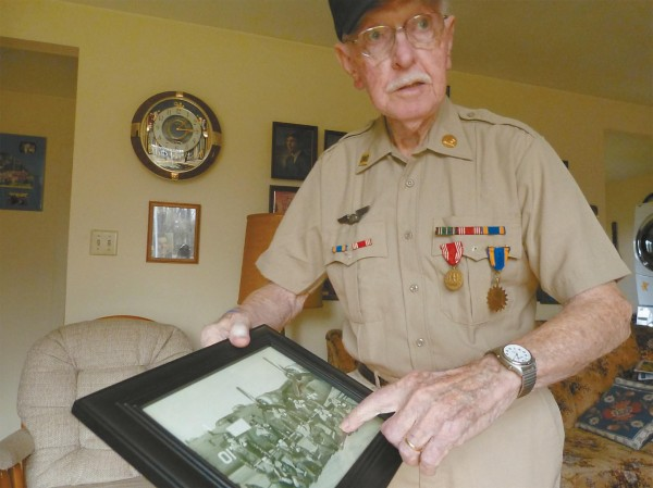 Joseph Bouchard of Bowdoin shows a photo of the flight crew in front of a B-24 from World War II.