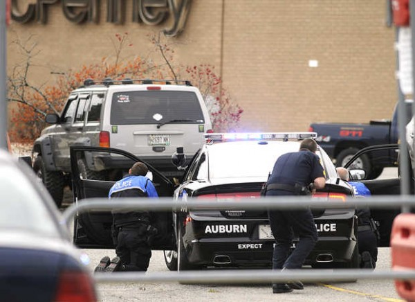 Auburn police officers take cover behind a police cruiser surrounding a suspect inside a Jeep Cherokee during a standoff at Shaw's Plaza in Auburn on Monday.