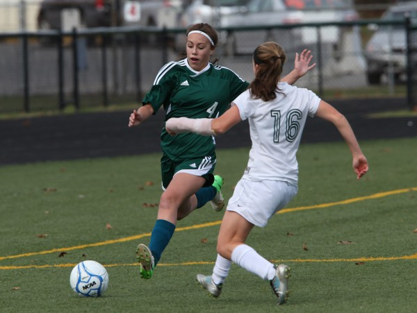 Fort Kent Warriors' Dakota Martin, left, joined by Waynflete Flyers' Leigh Fernandez, right, race to the ball during the Maine Principals' Association Class C Girls  Soccer State Championship Saturday, Nov. 3, at Scarborough High School in Scarborough, Maine