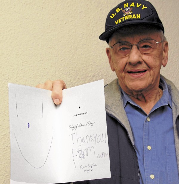 "Robert Treworgy, an 87-year-old World War II veteran from Calais, displays the smiley face and the ""thank you"" that a 6-year-old girl named Sophie wrote in a Veterans Day card (inset). Sophie stepped from the Bangor crowd during the Nov. 12 Veterans Day parade and handed the card in a sealed envelope to Treworgy. He was deeply moved when he later read the card."
