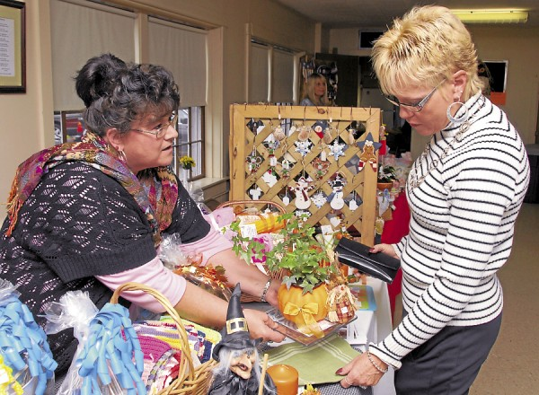 Dee Frederick of Dedham (right) purchases a Thanksgiving centerpiece from Marilyn Gray of Orrington during the Fall Craft Fair field Nov. 3 at the Dedham Congregational Church. Gray owns Hocus Pocus Gift Baskets.