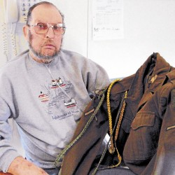 "Retired Winter Harbor lobsterman Douglas Torrey holds the ""Ike"" jacket that he was issued in 1946 as a member of the 1st Infantry Division."