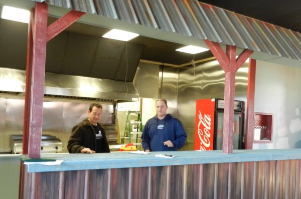 Keith Manaker (left) and Bob Cutler oversee the finishing touches at The Family Dog, a hot dog and burger restaurant they are opening soon at 6 Mill St. in Orono. The interior, designed by Chez Cherry, is meant to evoke a &quotcasual, divey&quot kind of place.