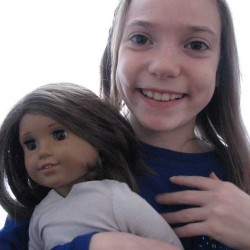 "Kaylynn Johnson of Norway holds Lucy, her American Girl doll. Johnson is a finalist in the video story contest ""Caroline's Share the Hero in You"" by American Girl. She is collecting cereal boxes to be used in Haiti to make jewelry and other items so parents can help pay for food, shelter and education for their children."