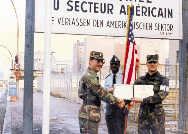 When the time came to re-enlist in the Army, military policeman Jesse Wilson II (right) did so in a ceremony held at Charlie Checkpoint separating West Berlin from East Berlin (background). According to Wilson, East German border guards watched in the distance as he re-enlisted right at the edge of the Berlin Wall.