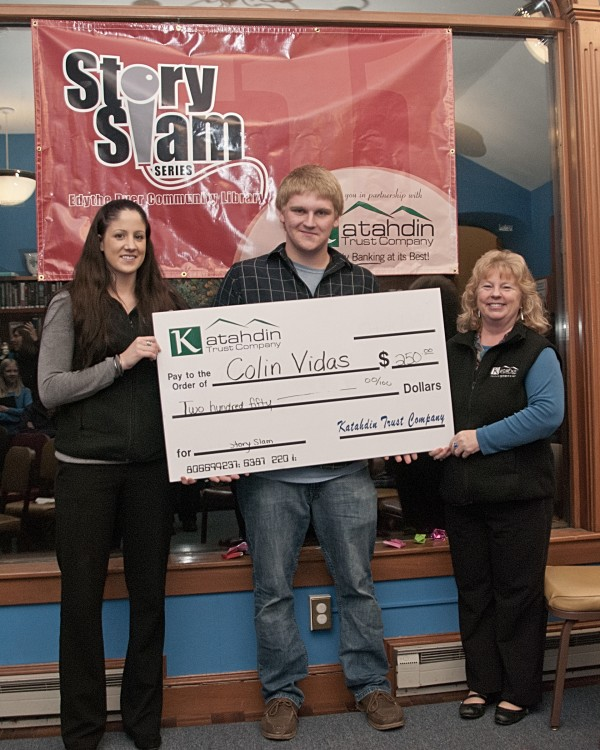 Colin Vidas accepts a check from Quinci Stewart, left and Sunny Somers representing Katahdin Trust Company.