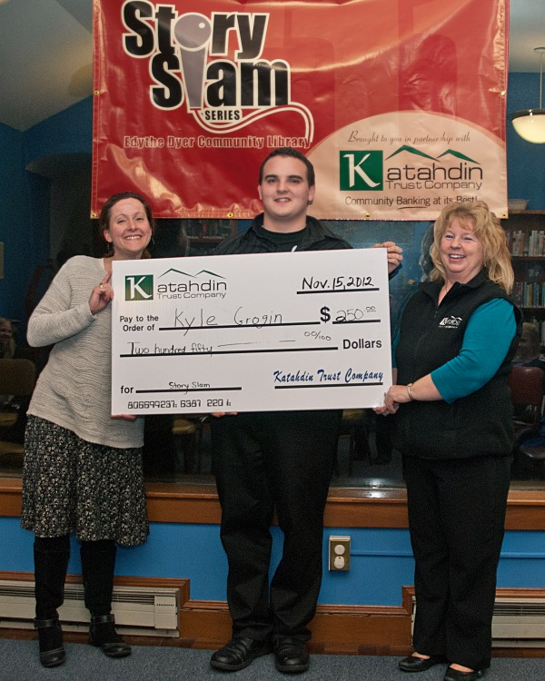 Mary Beckett, left and Sunny Somers present Story Slam winner Kyle Grogan a check for $250.00!