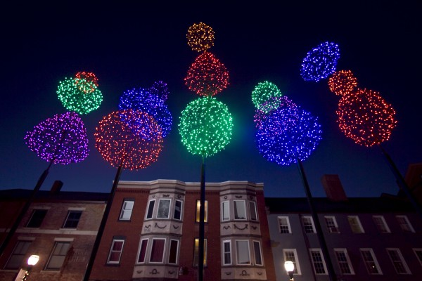 When viewed from below a cluster of colorful light balls evoke fireworks on Fore Street at dawn Thursday, Nov. 29, 2012, in Portland.