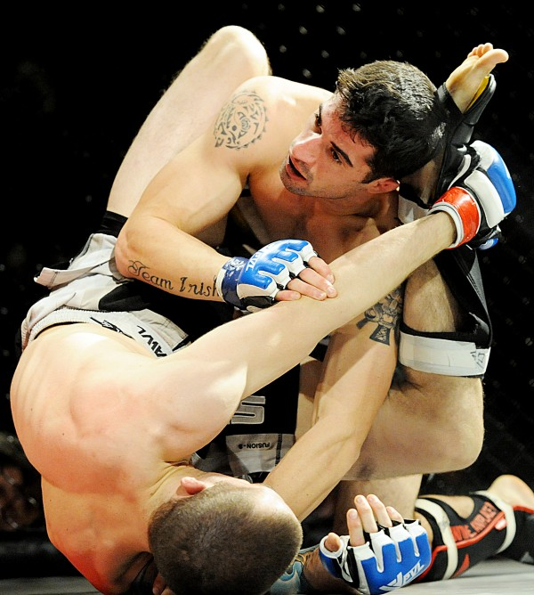 Tommy Balzano, top, gets tangled with Eilas Leland, both from Portland, during their bout Saturday night in Lewiston.  Leland, whom fights out of The Academy, won in 1:35 in the second round.