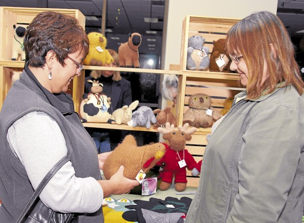 Checking out a Rhode Island Red hen pillow at the Holiday Marketplace Craft Fair held Nov. 3 at the Anah Shrine Center in Bangor are Dedham residents Marie Albert (left) and Robin Whitney. Albert owns Rhode Island Red hens.