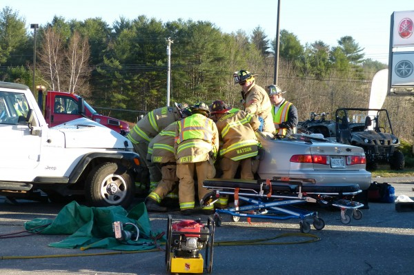 Topsham firefighters work to free the driver of a car involved in a two-vehicle crash at the Topsham Fair Mall this afternoon near Ruby Tuesday. Despite their efforts, the 79-year-old Brunswick woman died at the scene. The other driver was not injured.